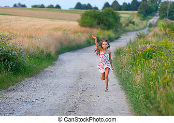 Bonita chica de siete años corriendo en la carretera de las Filds el día del verano