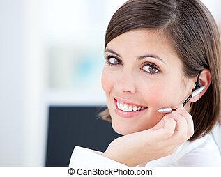 Bonita mujer de negocios hablando con clientes frente a su computadora en la oficina