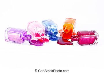 Botellas con esmalte de uñas derramado sobre fondo blanco