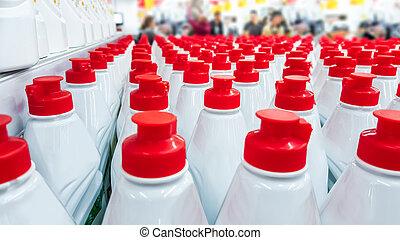 Botellas de plástico blancas con tapas rojas seguidas.