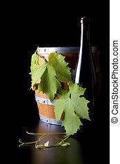 Botellas de vino, barriles y hojas de uva, fondo negro.