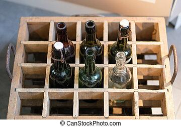 Botellas viejas en una caja de madera. Contiene cerveza o limonada.