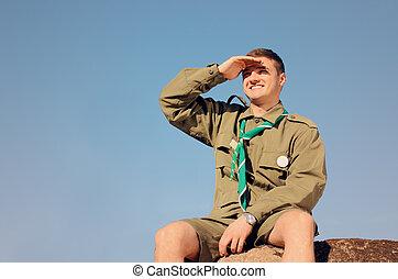 Boy Scout sentado en roca vigilando el campo