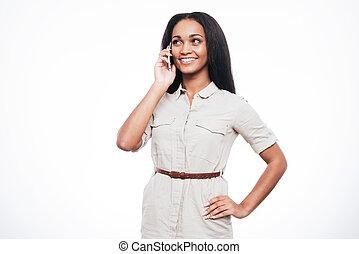 Buena charla. Hermosa joven africana hablando por teléfono móvil y sonriendo mientras se enfrenta a fondo blanco
