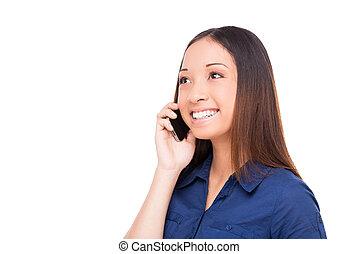 Buena charla. Hermosa joven asiática hablando por teléfono móvil y sonriendo mientras está aislada en blanco