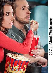 ¡Buena película! El primer plano de una pareja joven alimentándose mientras miramos la película en el cine