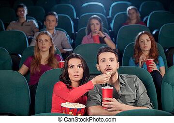 ¡Buena película! Una pareja joven alimentándose mientras veían películas en el cine