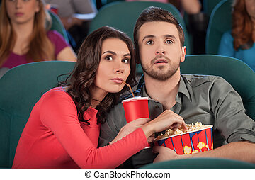 ¡Buena película! Una pareja joven comiendo palomitas de maíz y bebiendo soda mientras ve la película en el cine