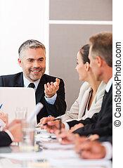 ¡Buenas noticias para nuestra compañía! Gente de negocios en ropa formal discutiendo algo mientras se sientan juntos en la mesa