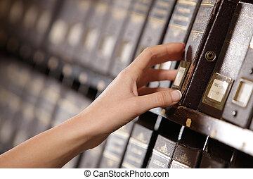 Buscando en los archivos. Manos de estudiante buscando en un armario de relleno.