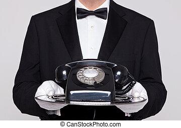 Butler sostiene un teléfono en bandeja de plata