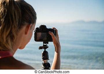 cámara, encima, vista, hembra, ajustes, hombro, fotógrafo, arreglar