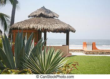 Cabana mexicana junto a la playa y el agua