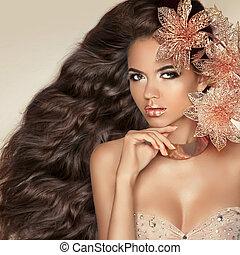 Cabello largo ondulado. Hermosa chica morena atractiva con flores.