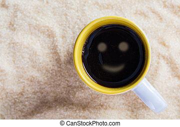 Café con leche con una taza sonriente en el fondo de azúcar.