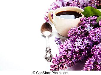 Café negro en una taza, una cuchara y flores lilas frescas