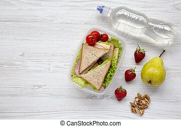 Caja de almuerzo saludable de la escuela con bocadillos de vegetales orgánicos frescos, nueces, botella de agua y frutas en fondo blanco de madera, plano. Desde arriba. La mejor vista. Copia espacio.
