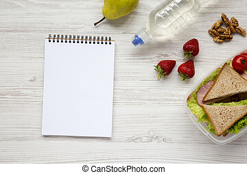 Caja de almuerzo saludable de la escuela con libreta sobre fondo blanco de madera, plano. Desde arriba. La mejor vista. Espacio para el texto.