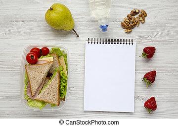 Caja de almuerzo saludable de la escuela con libreta sobre fondo blanco de madera, plano. Desde arriba. La mejor vista. Copia espacio.
