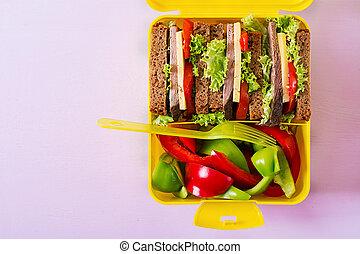 Caja de almuerzo saludable de la escuela con sándwich de carne y verduras frescas en el fondo rosa. La mejor vista. Planta