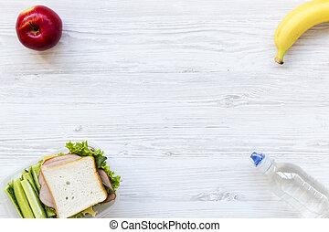 Caja de almuerzo saludable de la escuela con sándwich, frutas y una botella de agua sobre fondo blanco de madera, plano. Desde arriba. Copia espacio.