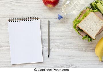 Caja de almuerzo sana con cuaderno y lápiz sobre fondo blanco de madera, plano. Desde arriba.