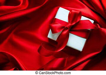 Caja de regalos de San Valentín con cinta roja de satén en el fondo de seda roja