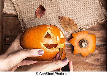 Calabaza para Halloween en manos de las mujeres, preparándose para las vacaciones de otoño. Hojas y decoración en una mesa de madera. La mejor vista.