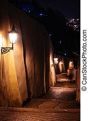 Callejón de escaleras con linternas en Praga por la noche