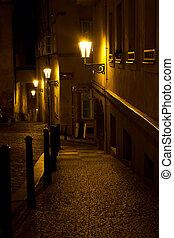 Callejón estrecho con linternas en Praga por la noche
