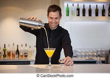 Camarero sonriente vertiendo cóctel amarillo en vidrio