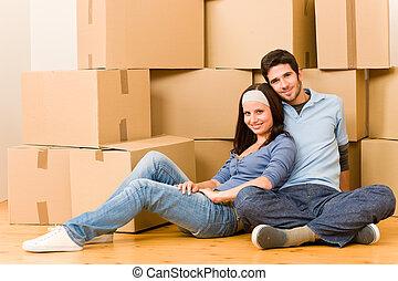 Cambiando de casa a la nueva pareja joven sentada
