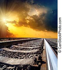 Camino a horizonte bajo un cielo dramático con sol
