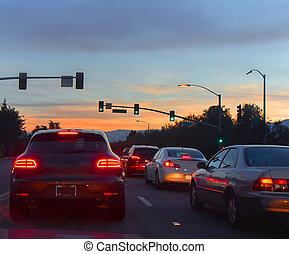 Camino con coches en el tráfico de la noche