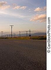 Camino y campo con postes eléctricos