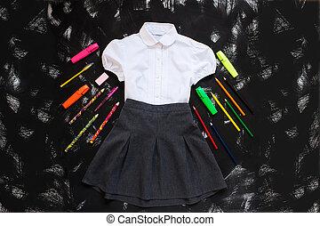 Camisa blanca, falda gris y artículos de papelería sobre fondo negro. El primero de septiembre, año nuevo.