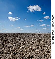 Campo negro bajo el cielo azul