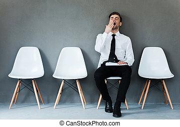 Cansado de esperar. Un joven hombre de negocios cansado sosteniendo papel y bostezando sentado en una silla contra el fondo gris