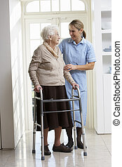 Carer ayudando a la anciana usando un marco andante