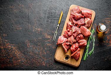 Carne cruda con romero, tenedor y aceite embotellado.