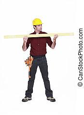 Carpenter sosteniendo una tabla de madera