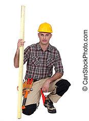Carpintero arrodillado con una tabla de madera