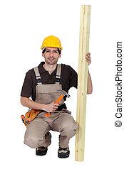 Carpintero con tabla de madera y martillo