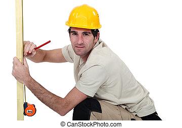 Carpintero marcando tablas de madera