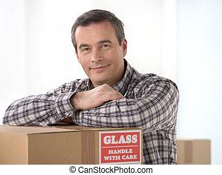 cartón, casa, moving., hombre, alegre, propensión, sonriente, caja, cuarentón