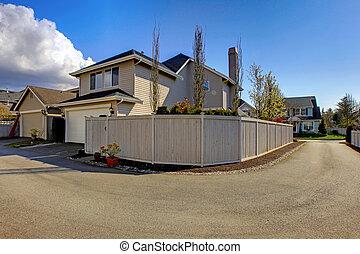 Casa de beige del patio con garaje y cerca de la carretera.