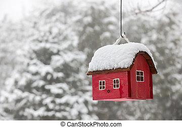 Casa de pájaros con nieve en invierno