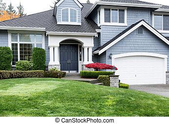 Casa limpia durante la temporada de otoño con arce rojo y jardín verde