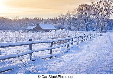 Casa rural con una cerca en invierno