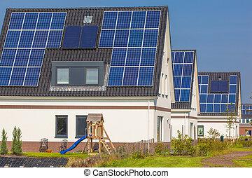 Casas nuevas con paneles solares en una calle moderna